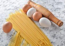 Макаронные изделия, яичка, свертывая на белой конкретной поверхности Варочный процесс, ингридиенты и инструменты кухни столового  Стоковые Изображения RF