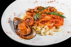 Макаронные изделия Fettuccine с морепродуктами, мидиями, осьминогом, устрицами, томатным соусом в шаре изолированном на черноте стоковое изображение rf