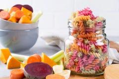 Макаронные изделия fusilli риса сухие от овощей в стеклянном опарнике Свои естественные vegetable краски сельдерей, свекла, морко стоковое фото