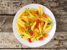 Макаронные изделия Penne при томаты украшенные с базиликом на старой деревенской серой деревянной предпосылке, диете низко-калори стоковое фото