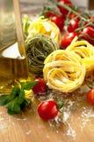 Макаронные изделия Tagliatelle со свежим базиликом и томаты на деревенской таблице стоковые фотографии rf