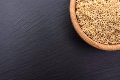 Макаронные изделия в форме звездочек лежат в деревянной чашке на черной каменной доске, космосе для текста Стоковое Изображение