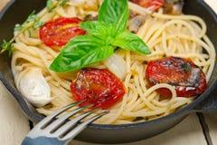 Макаронные изделия спагетти с испеченными томатами и базиликом вишни Стоковые Изображения