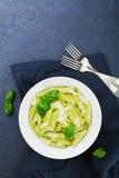 Макаронные изделия с соусом песто украсили листья и сыр пармесан базилика в белом блюде на голубой таблице сверху Стоковые Изображения