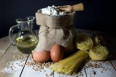 Макаронные изделия, 2 яичка, сумка джута заполненная с мукой, деревянная ложка и оливковое масло в стеклянной бутылке на деревянн Стоковые Изображения