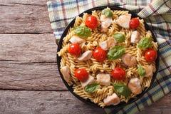 Макаронные изделия Fusilli с цыпленком, томатами и базиликом на плите горизонт Стоковое Изображение