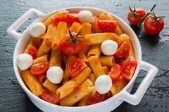 Макаронные изделия Penne с соусом, сыром моццареллы и томатами вишни в белом круглом лотке на черной каменной предпосылке Стоковые Фото