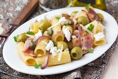 Макаронные изделия Rigatoni с беконом, зелеными оливками, сыром фета, красный лук, Стоковое Фото