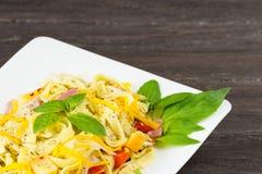 Макаронные изделия Tagliatelle с соусом песто, беконом, сыром Gauda, чеддера, Эмменталя и базиликом выходят в белую плиту на серу Стоковое Изображение RF