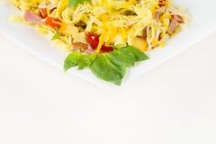 Макаронные изделия Tagliatelle с соусом песто, беконом, сыром Gauda, чеддера, Эмменталя и базиликом выходят в белую плиту на белу Стоковые Изображения RF