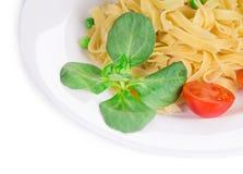Макаронные изделия Tagliatelli с томатами и базиликом Стоковое Фото