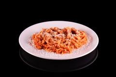 Макарон спагетти макаронных изделий с сыр пармесаном на белой плите на черной предпосылке Стоковые Изображения RF