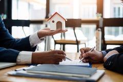 Маклер по операциям с недвижимостью объясняет вклад контракта перед подписанием жилого массива контракта в офисе концепция контра стоковые фото