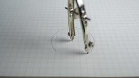 Макрос компаса рисуя круг на бумаге конец вверх акции видеоматериалы