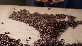 макрос кофе завтрака фасолей идеально изолированный над белизной Руки разбросали кофейные зерна Кофейные зерна касания рук ` s же сток-видео