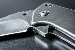 Макрос половинного открытого черного складывая ножа на темной земле Стоковое Изображение