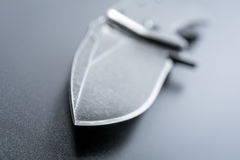 Макрос пункта ножа раскрытого черного складывая ножа который лежит на темной земле Стоковые Фото