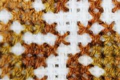 Макрос снял вышивку потока коричневого цвета картины вышивки части handmade, картину в стиле вышивки крестиком на белой ткани Стоковая Фотография RF
