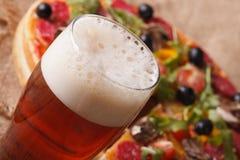 Макрос холодного пива на предпосылке пиццы на таблице Стоковое фото RF