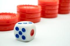 Максимальное число кости придавать против стога красной монетки поднимая Стоковые Фото