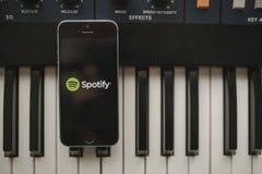МАЛАГА, ИСПАНИЯ - 12-ое апреля 2018: Spotify течь музыка app в экране iPhone, помещенном на винтажной музыкальной клавиатуре стоковое фото rf