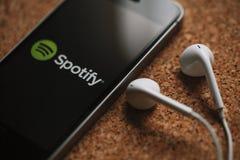 МАЛАГА, ИСПАНИЯ - 5-ОЕ МАРТА 2018: Мобильный телефон с логотипом Spotify в экране и белых наушниках, помещенных на панели пробочк стоковое изображение rf