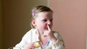 Малая девушка имеет закуску Милая маленькая девочка ест распространение сливк шоколада на крене скрепляет болтами гайки семьи при акции видеоматериалы