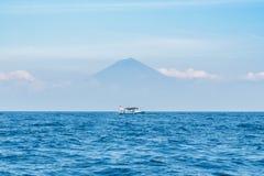 Малая деревянная шлюпка на голубом океане с ясными небом и держателем Agung на предпосылке bali Индонесия стоковые фотографии rf