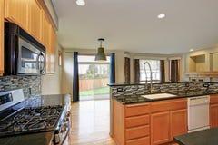 Малая компактная комната кухни с светлым деревянным cabinetry стоковое изображение