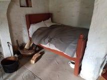 Малая кровать с деревянными журналами и стенами ночного горшка и белых Стоковое Изображение RF