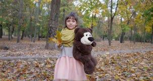Малая прогулка девушки с плюшевым медвежонком и желтым цветом выходит в руки на парке осени, играя с игрушкой outdoors акции видеоматериалы
