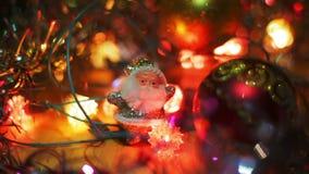 Малая серебряная диаграмма Санта Клауса стоит около красной безделушки смертной казни через повешение рождества на таблице Мерцан сток-видео