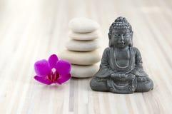 Малая скульптура Будды, камешки пирамида из камней, 5 белых камней, один фиолетовый цветок орхидеи фаленопсиса стоковое изображение rf