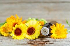 Малая стеклянная бутылка на старых деревянных цветках предпосылки и calendula, конце вверх Ароматерапия, курорт и фитотерапия Стоковое Фото