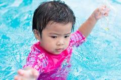 Маленькая азиатская попытка девушки плавая самостоятельно в бассейне, внешнем стоковое изображение rf