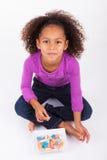 Маленькая африканская азиатская девушка есть конфету Стоковое фото RF