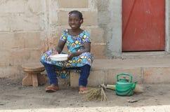 Маленькая африканская девушка варя рис Outdoors усмехаясь на камере Стоковые Изображения RF