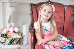 Маленькая белокурая девушка в красочном платье сидя на большой софе стоковое фото