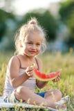 Маленькая белокурая девушка есть арбуз в парке стоковая фотография rf