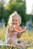 Маленькая белокурая девушка есть арбуз в парке стоковое изображение rf