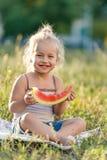 Маленькая белокурая девушка есть арбуз в парке стоковое изображение