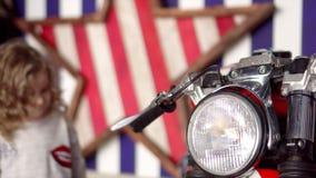 Маленькая белокурая девушка с ringlets рассматривает большой винтажный мотоцикл в студии Маленькая девочка смущается внутри видеоматериал