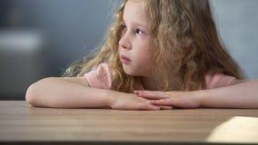 Маленькая белокурая курчавая грустная девушка сидя на таблице и думая о собственном поведении стоковые фото