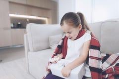 Маленькая больная девушка сидит на белом кресле обернутом в красном шарфе Она чихает, принимающ вне салфетку стоковые изображения