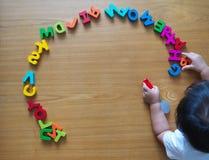 Маленькая верхняя часть малыша вниз осматривает с ее игрушками Стоковые Фото