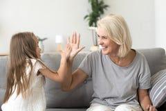 Маленькая внучка и счастливая бабушка давая высоко 5 игру стоковые изображения