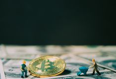 Маленькая горнорабочая выкапывает для валюты золотого bitcoin цифровой na górze 100 предпосылок банкнот доллара Стоковая Фотография