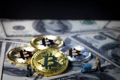 Маленькая горнорабочая выкапывает для валюты золотого bitcoin цифровой na górze 100 предпосылок банкнот доллара Стоковое Изображение RF