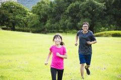 Маленькая девочка бежать в сельской местности с отцом Стоковое Изображение RF