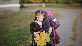 Маленькая девочка бежит домой от школы к объятию ` s мамы Мать встречает дочь от школы видеоматериал